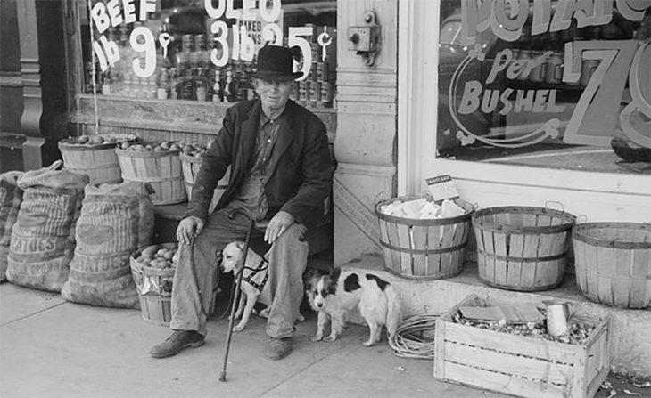 Un hombre y su perro frente a una tienda en Illinois, 1940