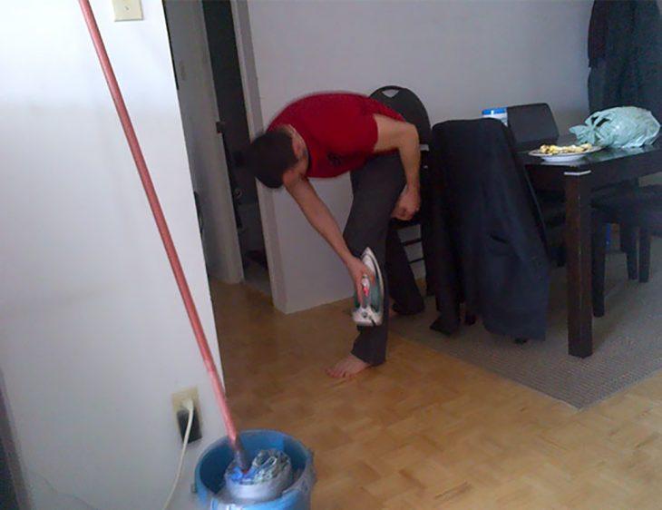 hombre planchándo su pantalon cuando lo tiene puesto