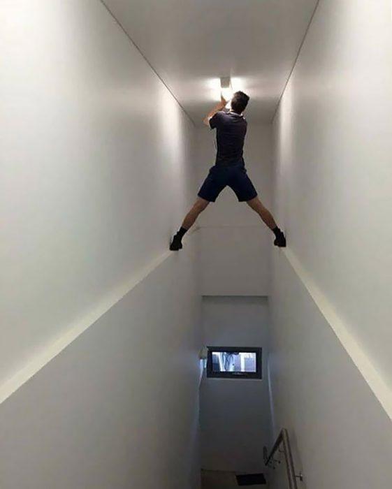 chico poniendo un foco en un techo sin escaleras apuntado solo en las puntillas