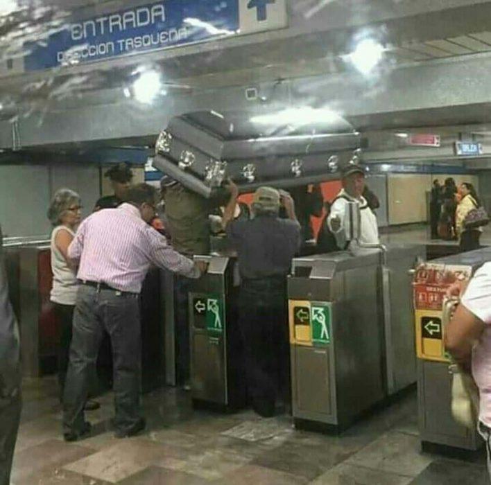 hombres cargando un ataúd antes de subir al metro