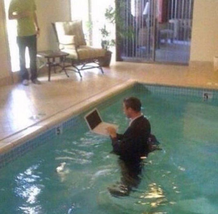 hombre en piscina con laptop