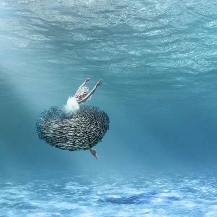 imagen surrealista de mujer bajo el mar con su falda hecha de peces