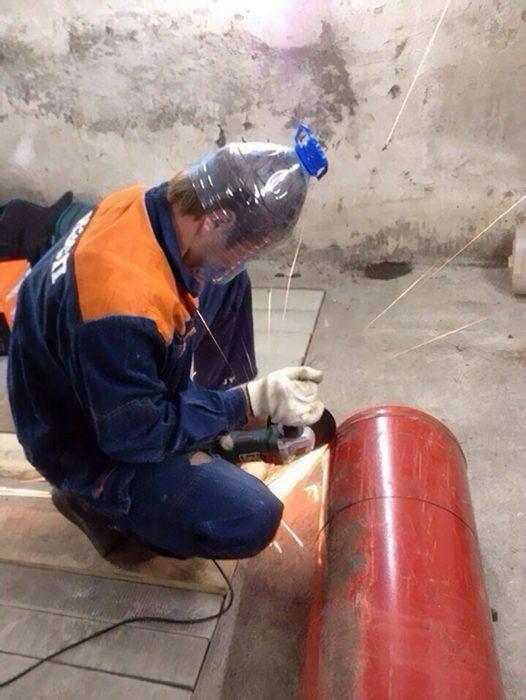 hombre con casco hecho de una botella soldando algo