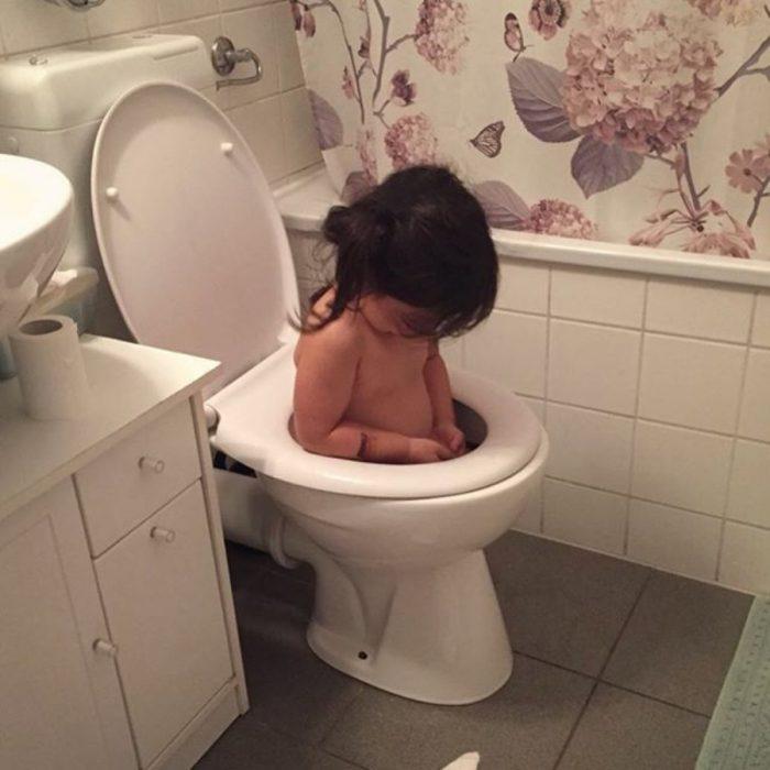 niña dentro de una taza de baño
