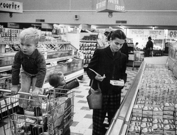 Una madre trabajadora haciendo las compras junto a sus hijos, 1956