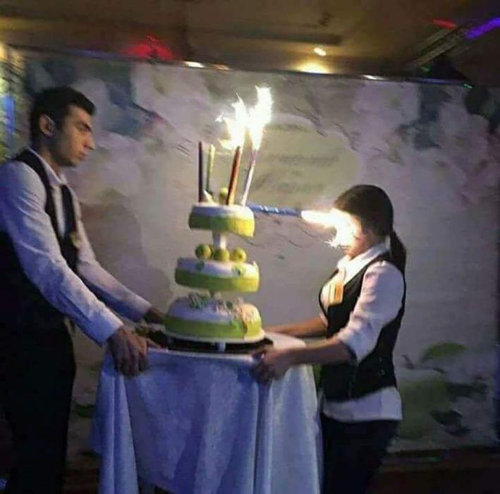 dos personas cargando un pastel fail