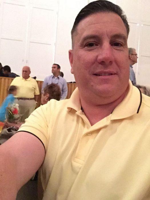señor con camisa amarilla y detrás un señor mayor con la misma camisa