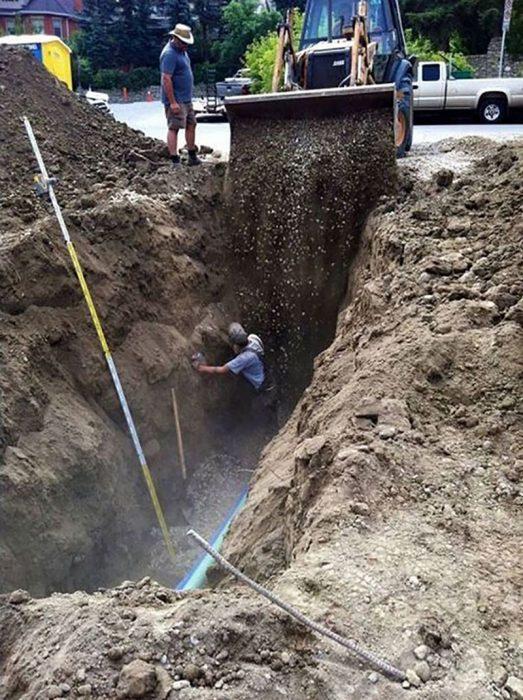 hombre con maquina enterrando a compañero de trabajo