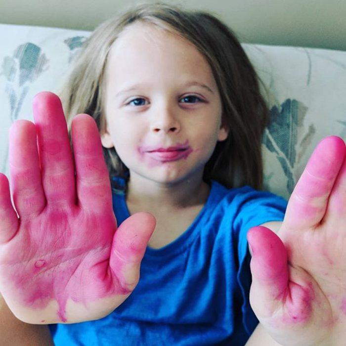Niño con las manos manchadas de rosa
