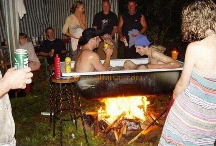 hombres en una bañera sobre el fuego