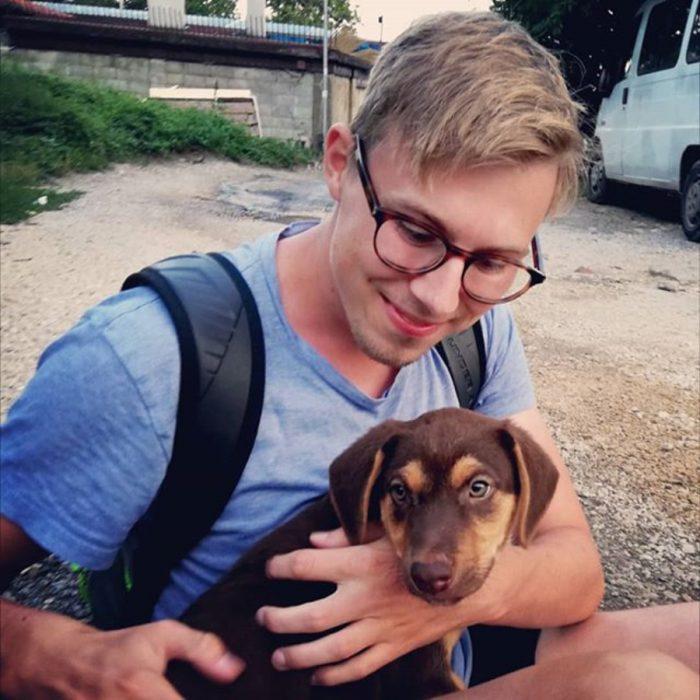 muchacho abrazando a un perrito de la calle