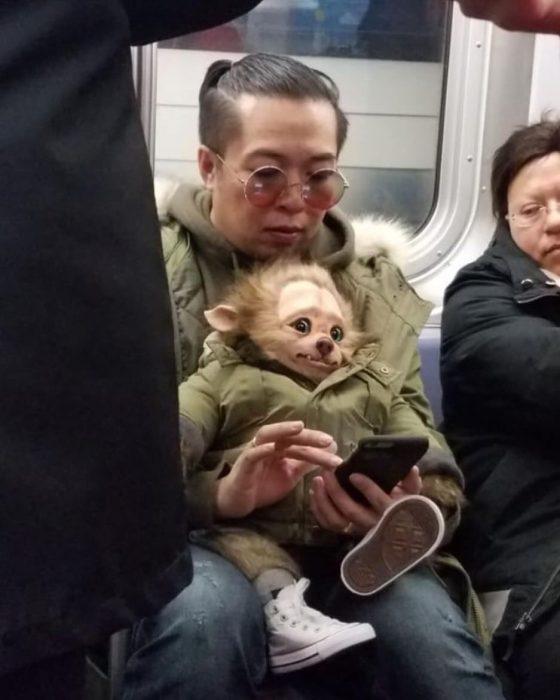 hombre cargando un muñeco monstruo en el metro