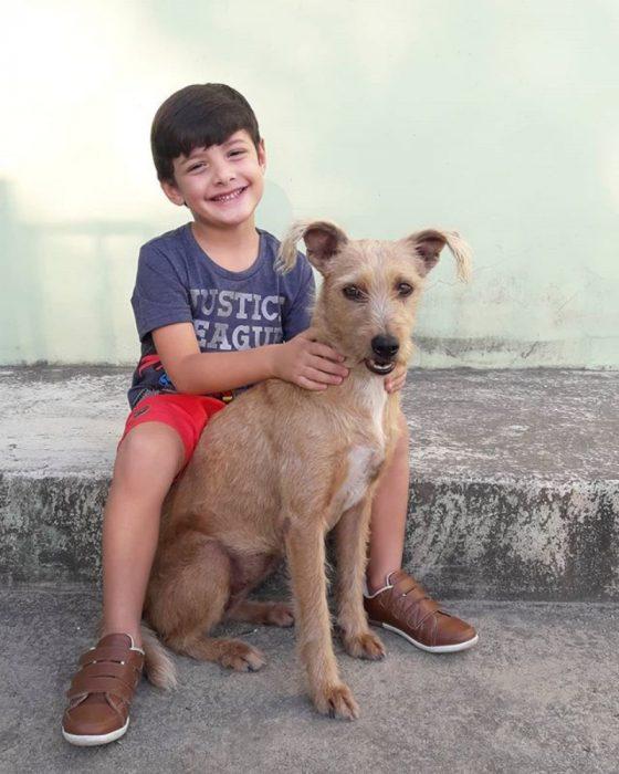 niño sonriendo al lado de un perrito