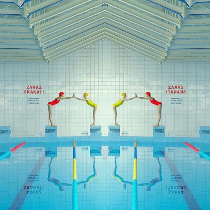 parejas en nado sincronizado reflejándose en la alberca
