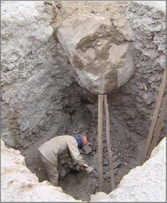 palos sosteniendo una enorme roca