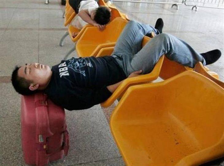 chino dormido con cabeza en su maleta