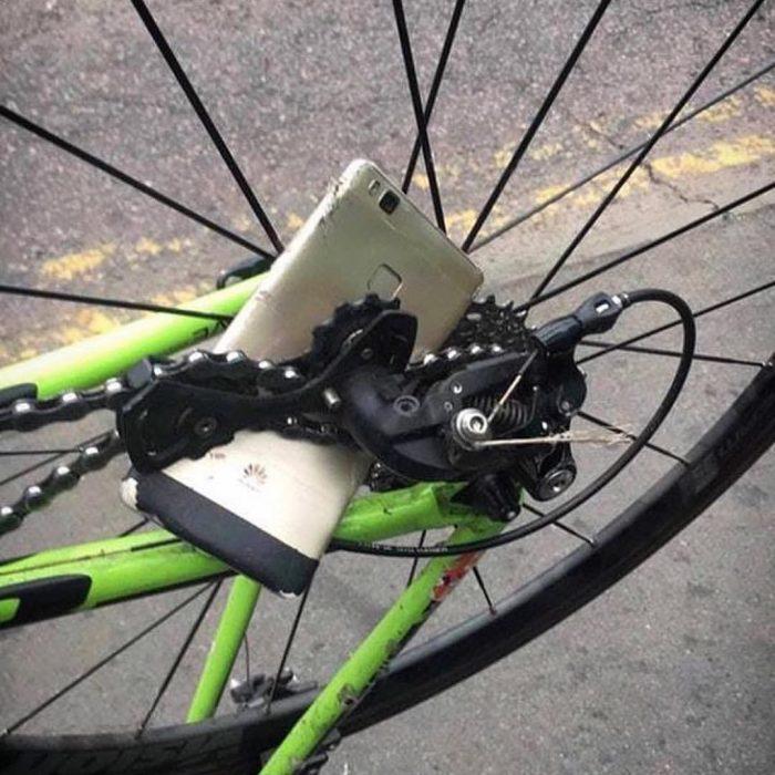 celular atorado en los rines de una llanta de bicicleta