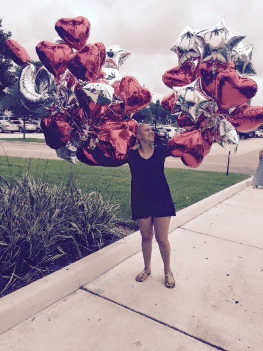 muchacha con muchos globos de corazones