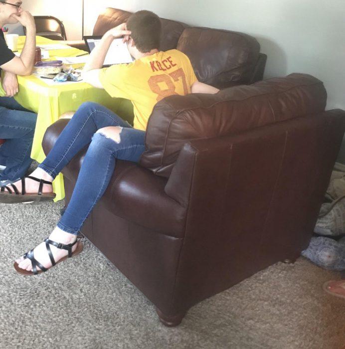 chico en silón que por perspectiva parece una chica