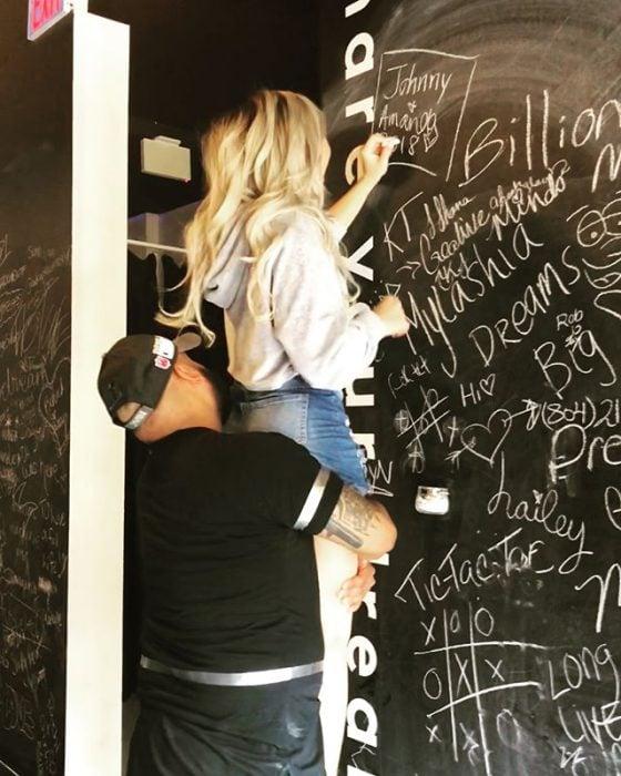 hombre cargando a una mujer para que escriba en un pizarrón