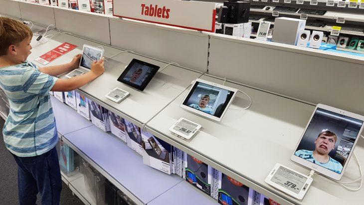 niño pone su cara de wallpaper en los celulares de una tienda