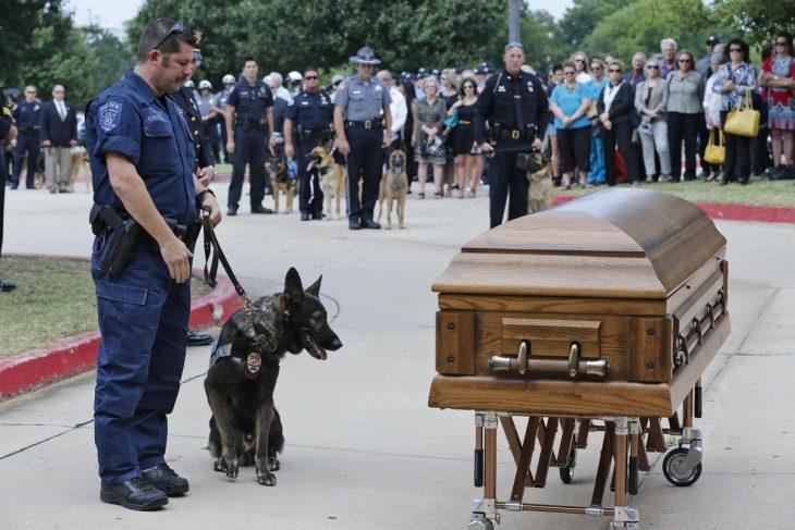 policía y k9 frente a un féretro