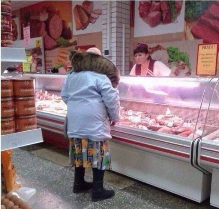señora comprando carne con su gato en el hombro