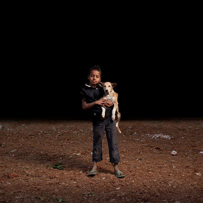 niño de bangladesh cargando a su masctoa