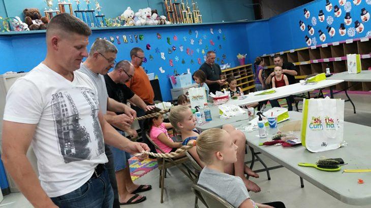 Papás tomando clases para peinar a sus hijas