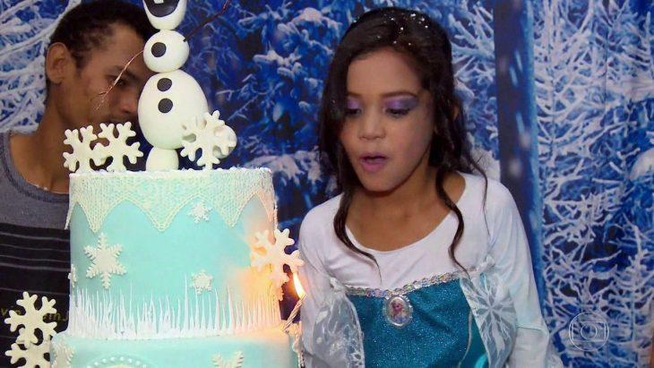 niña soplando las velas de su pastel