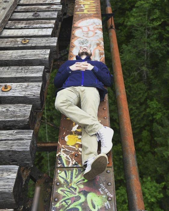hombre recostado en un puente