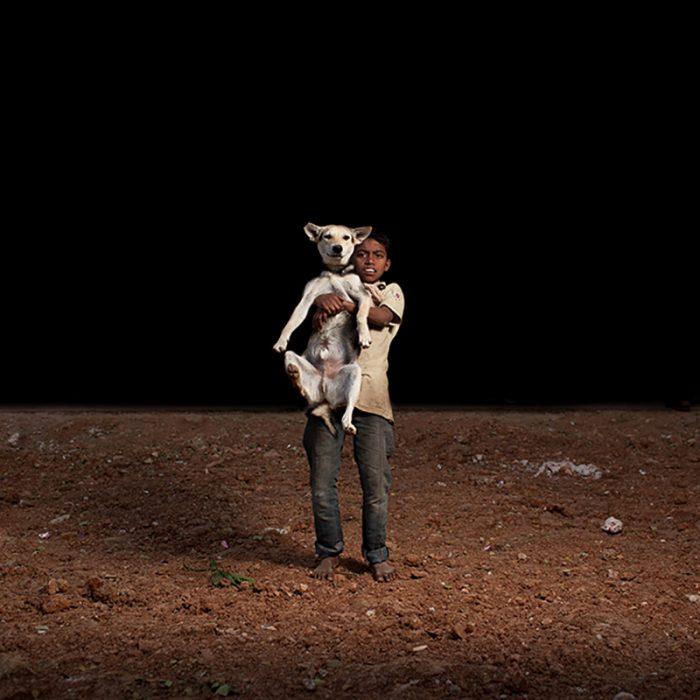 niño de la calle con perrito de la calle en brazos