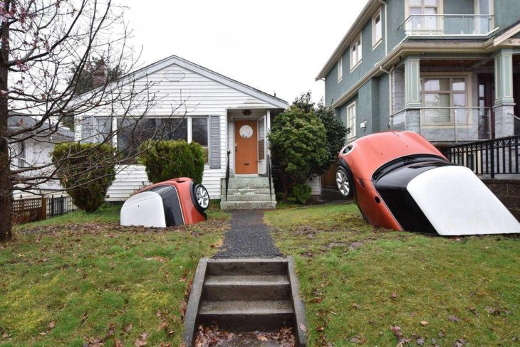 autos enterrados en la tierra frente a una casa