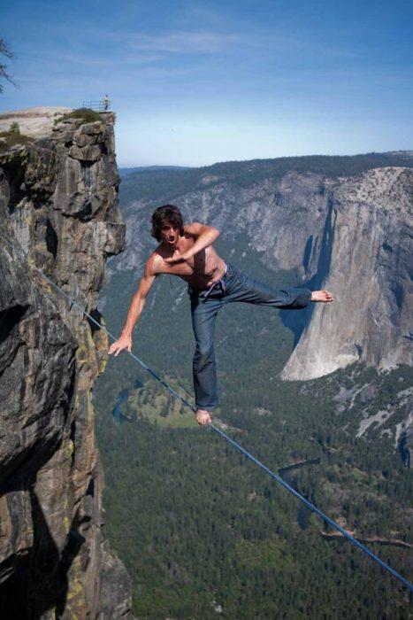 hombre sin arnés en una cuerda sobre las montañas