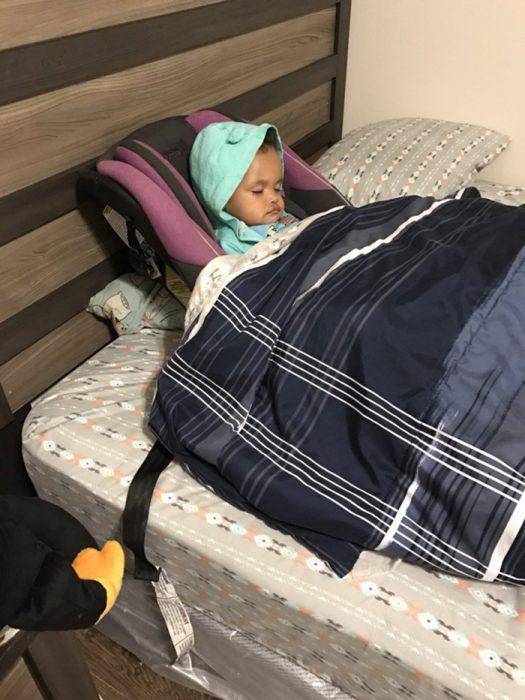 bebé en cama con asiento de coche
