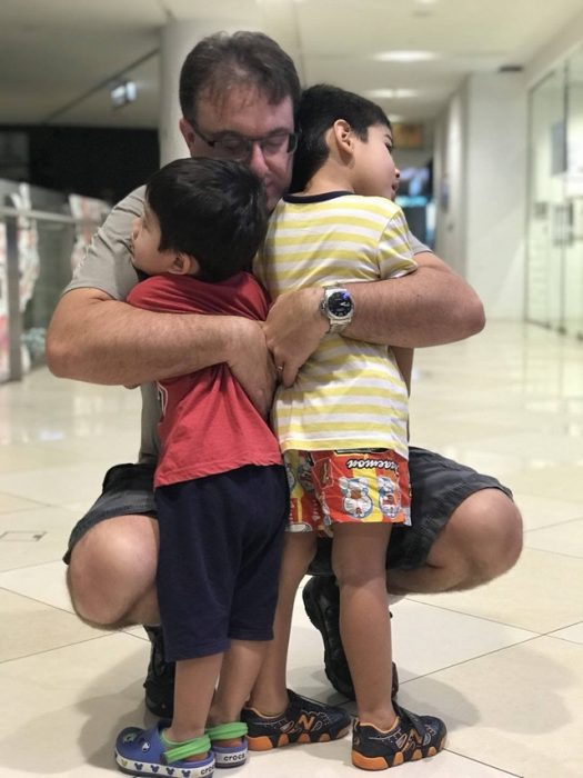 hombre abrazando a sus dos hijos