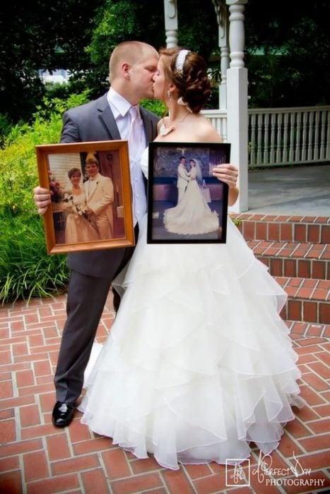 Sosteniendo fotos de las bodas de sus padres