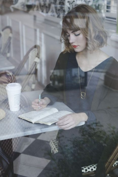 mujer escribiendo en un café