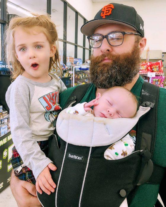 hombre cargando a sus dos bebés