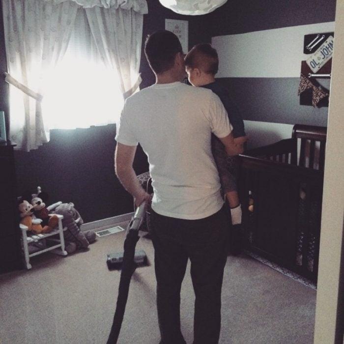 papá cargando bebé y aspirando
