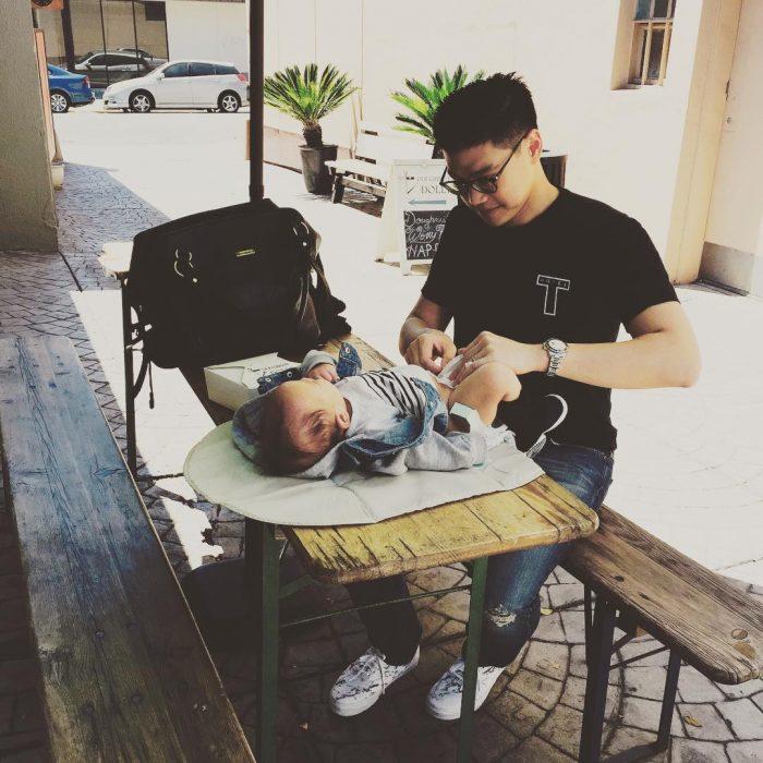 hombre que le cambia los pañales a su hijo