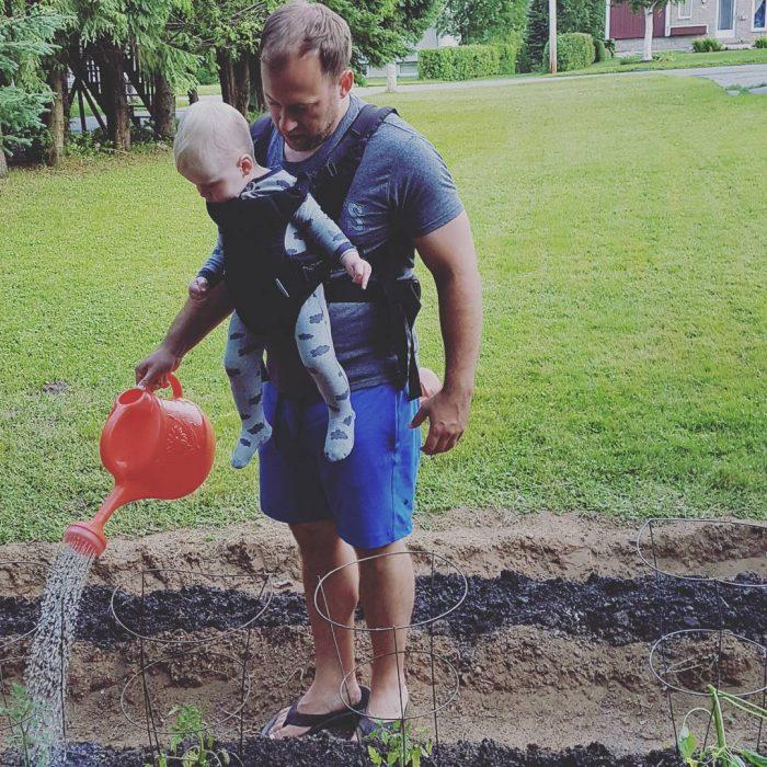 hombre con bebé regando las plantas