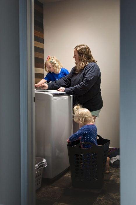 mamá en lavadora con dos niñas