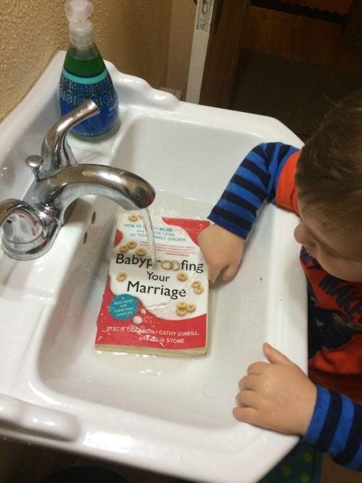 niño mojando un libro