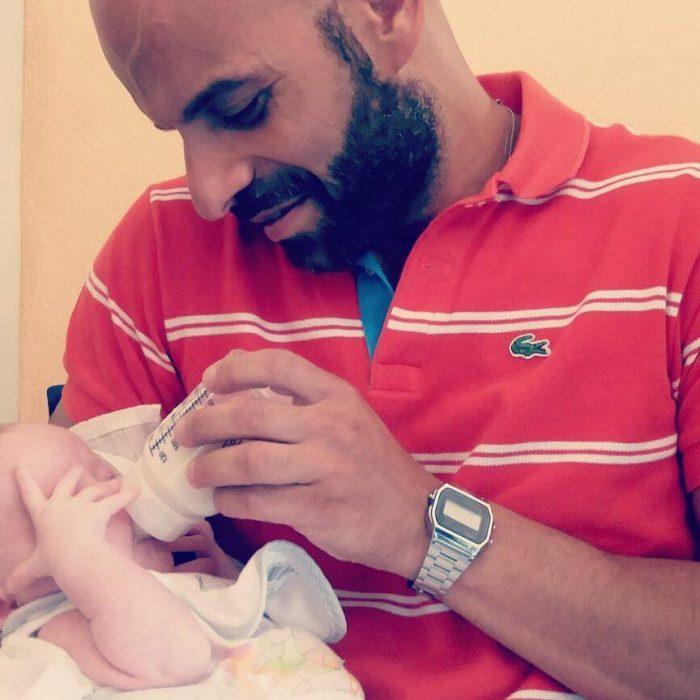 hombre dando biberón a una bebé