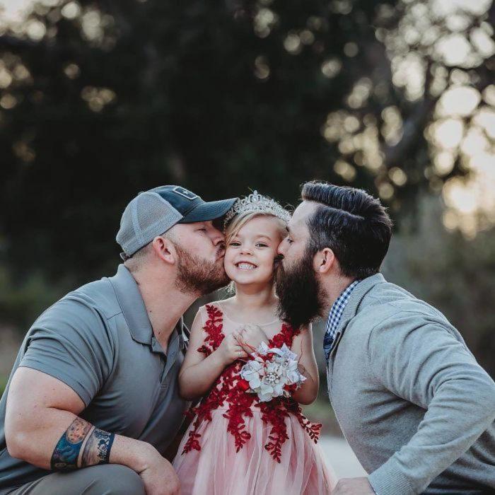 papás besando a niña